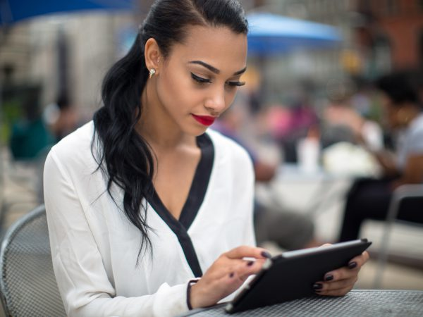 Young beautiful business woman using ipad tablet outdoor